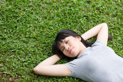 Asian woman lying sleeping on grass. Royalty Free Stock Photo