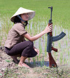 Asian woman with a machine gun. In a paddy field stock photos