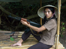 Asian woman with a machine gun. Woman with a machine gun sits in a bamboo shelter stock photos
