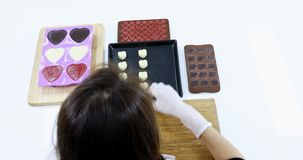 Asian woman made chocolate for Valentine`s day. Asian woman setting white heart shaped chocolate on baking tray, many size of heart shaped chocolate on table stock video