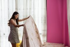 Asian woman make bed after waking up. Attractive Asian beautiful woman making bed after waking up in the morning. girl in pink bedroom keep blanket in good Royalty Free Stock Photo