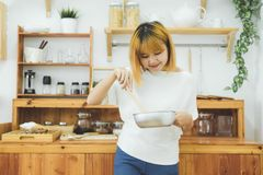 Asian woman making healthy food standing happy smiling in kitchen preparing salad. Beautiful cheerful Asian young woman at home. Healthy food dieting and Royalty Free Stock Photography