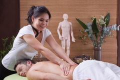 Asian woman making massage for a man Royalty Free Stock Image