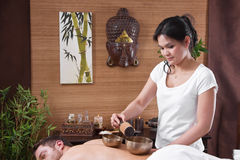 Asian woman making massage to a man Stock Image