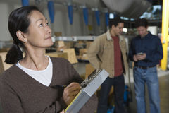 Asian Woman Making Notes In Distribution Warehouse Stock Image