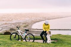 Free Asian Woman Making Uphill With Mountain Bike. A Woman Playing With A Dog At Lookout Point Oamaru, New Zealand Royalty Free Stock Photos - 179723498