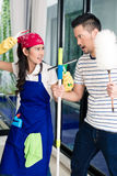 Asian woman and man having fun cleaning home Stock Photos