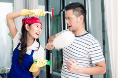 Asian woman and man having fun cleaning home. Asian women and men having fun cleaning home staging a mock fight with chores utensils stock photos