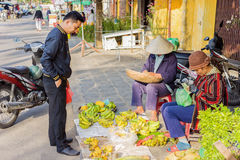 Asian woman and man selling bunches of bananas Royalty Free Stock Photography