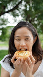 Asian woman mature adult eating bread carbohydrates. Green background royalty free stock image
