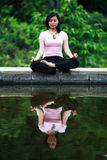Asian Woman Meditating. By a lotus pond Stock Photos