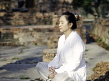 Asian woman meditating in ancient buddhist temple Royalty Free Stock Images
