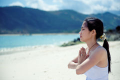Asian woman meditating on the beach Stock Image