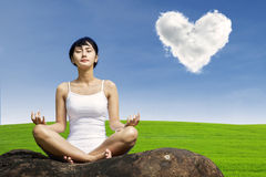 Asian woman meditating at green field Royalty Free Stock Photography