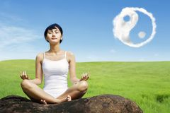 Asian woman meditating outdoors on the rock at meadow with yin yang clouds symbol in the sky royalty free stock photo