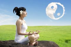 Asian woman meditating outdoors on the rock at meadow with yin yang clouds symbol in the sky royalty free stock image