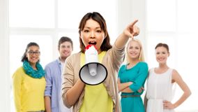 Asian woman with megaphone over group of people. Announcement, diversity and human rights concept - asian young women speaking to megaphone over international royalty free stock photos