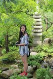 Asian Woman Model Stands Near Sculpture in Forest Royalty Free Stock Photos