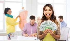 Asian woman with money over fashion design studio. Education, funding and fashion design, concept - happy asian young women holding hundreds of euro money stock photography