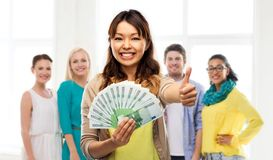 Asian woman with money showing thumbs up. Winning, saving and finances concept - happy asian young women holding hundreds of euro money banknotes and showing royalty free stock images