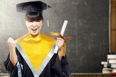 Asian woman in mortarboard hat and diploma graduating from college in the classroom with piles of books and blackboard background royalty free stock images