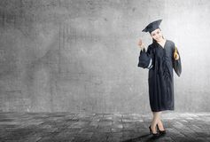 Asian woman in mortarboard hat and diploma graduating from college stock image