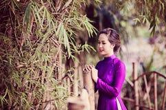 Asian woman near bamboo