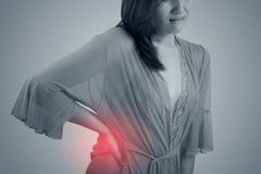 Asian woman in nightwear with pain in waist and back pain at night royalty free stock images