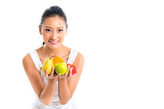Asian woman offering healthy fruits. Young Asian woman offering fruits for healthy living wearing sportswear Stock Photos