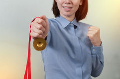 Asian Woman in office uniform holding a gold medal, Successful b. Working woman holding a gold medal, Successful business concept royalty free stock image