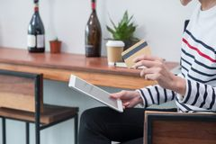 Asian woman online shopping using credit card with tablet comput. Er at cafe restaurant,Digital lifestyle concept,mobile banking Royalty Free Stock Image