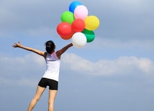 Asian woman open arms on mountain peak rock with colored balloons Royalty Free Stock Images