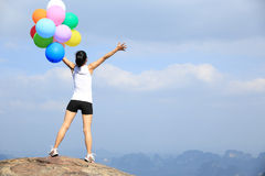 Asian woman open arms on mountain peak rock with colorful balloon Royalty Free Stock Image