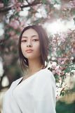 Asian woman outdoors on spring against flower blossom. Gorgeous asian woman with perfect skin creartive art make-up wearing trendy white japanese kimono standing stock photography