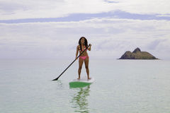 Asian woman on a paddle board Royalty Free Stock Photos