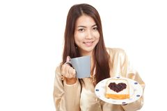 Asian woman in pajamas with coffee and heart shape jam on bread Stock Images