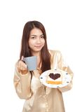 Asian woman in pajamas with coffee and heart shape jam on bread Stock Photos