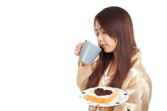 Asian woman in pajamas with coffee and heart shape jam on bread Stock Image