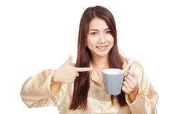 Asian woman in pajamas point to toothbrush in mug Stock Photo