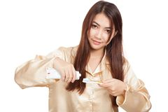 Asian woman in pajamas smile with toothbrush and toothpaste. Isolated on white background Stock Photo