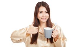 Asian woman in pajamas thumbs up with toothbrush in mug Royalty Free Stock Image
