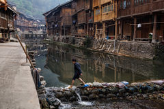 Asian woman passes countryside river on stones of dam, China. Stock Image