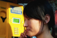Asian woman on a pay telephone Royalty Free Stock Images