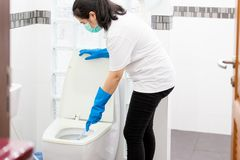 Asian woman people in blue glove with medical mask cleaning toilet bowl using brush and detergent,female housekeeper with face. Mask protection cleaning,wash royalty free stock photography