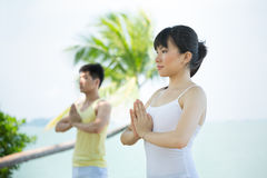 Asian woman performing yoga at the coast. Royalty Free Stock Image