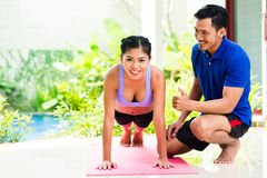 Asian woman and personal trainer at sport exercise Royalty Free Stock Images