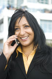 Asian woman on phone. A beautiful asian businesswoman enjoys a friendly chat on her cellphone.Office buildings are behind her Stock Images