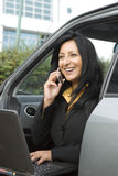 Asian woman on phone. A beautiful asian businesswoman enjoys a friendly chat on her cellphone while sitting in her car and working on her laptop computer Stock Photo