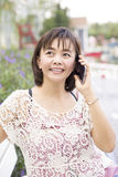 Asian woman phoning at home in garden Stock Image