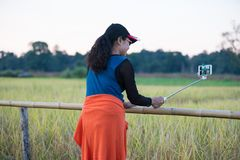 Asian woman photograph herself with selfie stick. Asian woman photograph herself by smart phone with selfie stick in paddy field background Royalty Free Stock Photography